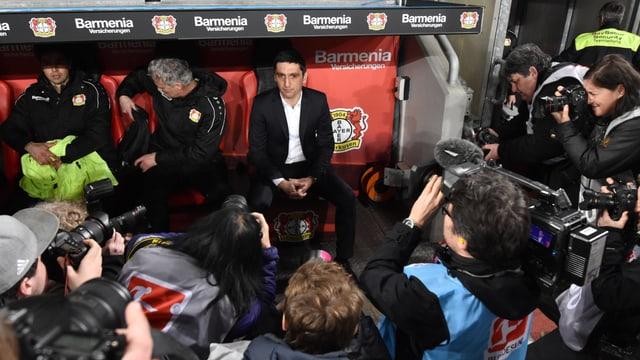Neo-Bayer-Trainer Tayfun Korkut sitzt - umringt von Fotografen - auf der Bank.