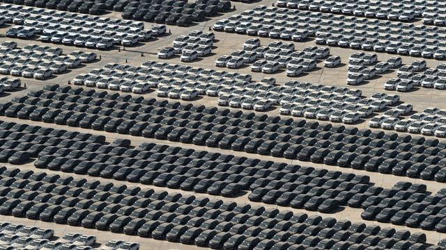 Blick von oben auf zahlreiche graue und schwarze Autos auf einem Platz.