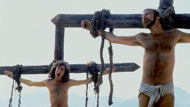 Zwei Männer hängen an Kreuzen und singen.