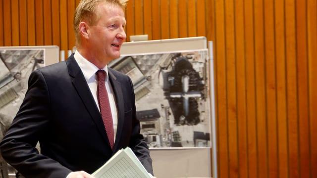 Innenminister Ralf Jäger vor einer Holzwand im Düsseldorfer Landdtag an der Luftaufnahmen hängen
