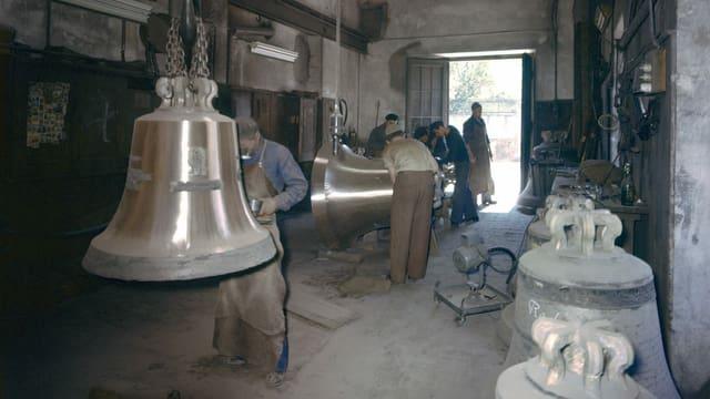 Grosse Glocken hängen vor Arbeitern an der Decke.
