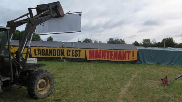 Das seit Jahren besetzte Gelände: An Zelten sind grosse Transparente angebracht mit der Aufschrift: «L' abandon c'est maintenant!» (Aufgabe ist jetzt).