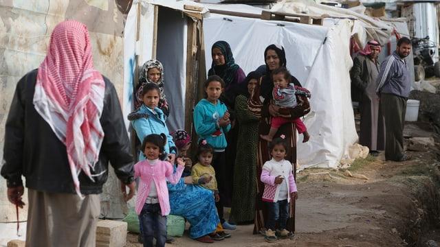 Frauen und Kinder vor einem weissen Zelt.