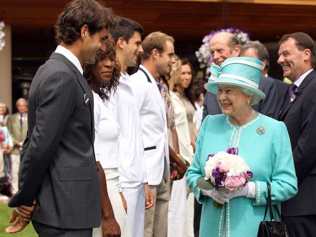 DIe Queen mit Roger federer auf dem Rasen von Wimbledon.