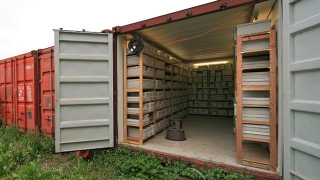 In einem alten Container lagern in Holzregalen alte steinerne Fundstücke aus dem Altertum.