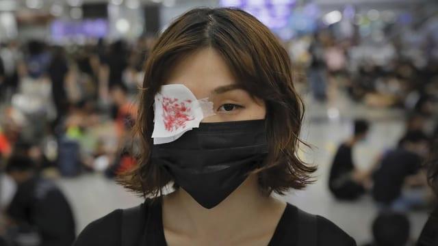 Frau mit rot-weisser Augenbinde