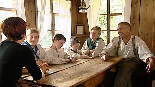 Die Familie sitzt mit der Moderatorin an einem Tisch.
