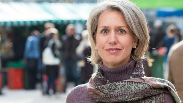 Eine Frau mit Foulard mit Marktständen im Hintergrund.