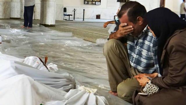 Ein älteres Paar trauert über Todesopfer in weissen Leichensäcken