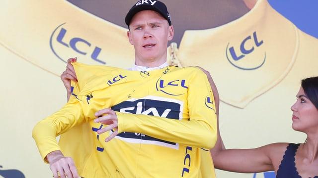 Chris Froome zieht das gelbe Trikot an.