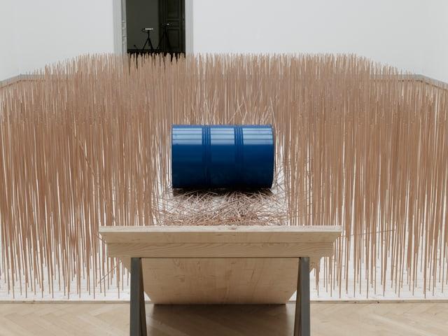 Ein blaues Fass liegt in einem Feld dünner Holzstäbe, davor eine Rampe aus Holz.