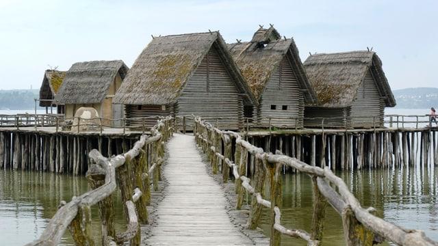 Eine Ansammlung von Pfahlbauerhäuser über Wasser mit einem Steg, der zu ihnen führt.