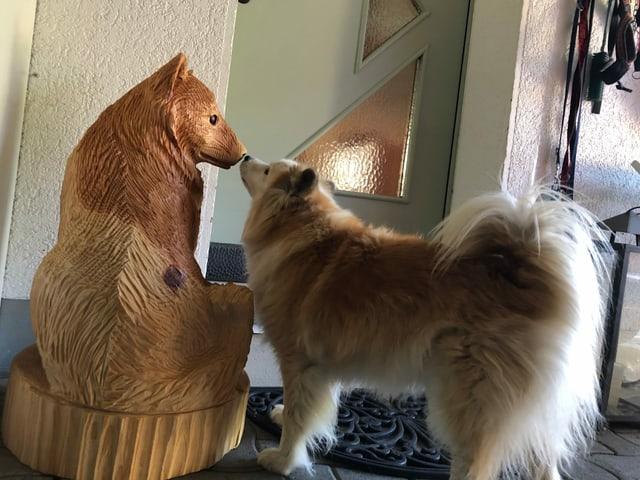 Ein Hund schnüffelt an einer Holzfigur.