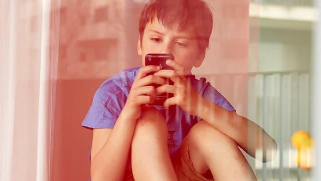 Ein Junge sitzt hinter einer Glasscheibe und schaut aus sein Handy.