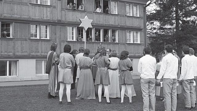 Kinder schauen aus dem Fenster. Draussen Besucher.