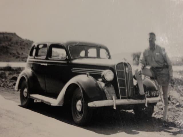 Ein junger Mann mit Hemd und kurzen Hosen steht neben einem Fahrzeug.