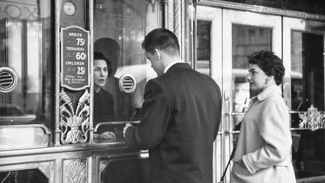 Zwei Menschen kaufen Kinokarten