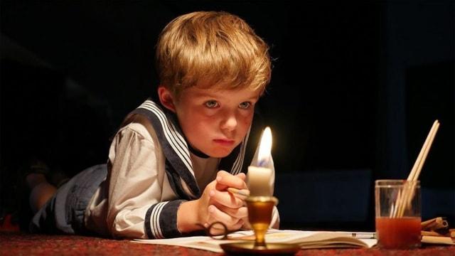 Ein kleiner Junge vor einer Kerze