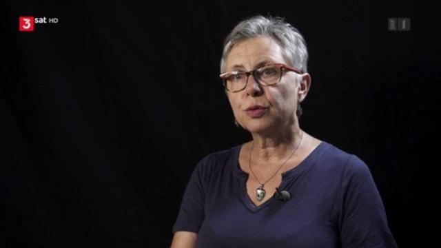 Eine Frau mit grauem Haar vor schwarzem Hintergrund.