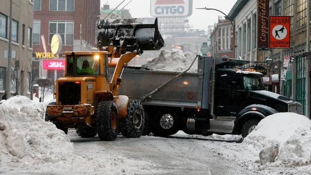 Mit Pneuladern werden die Schneemassen aus den Strassen auf Lastwagen geladen.