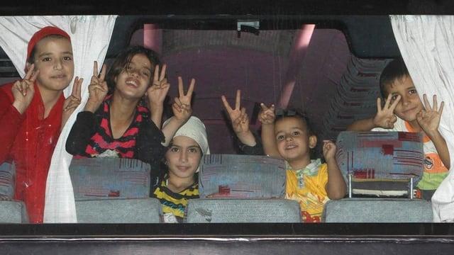 Kinder machen in einem Busfenster Siegeszeichen.