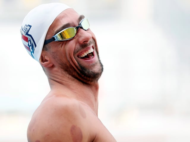 Michael Phelps lacht mit Badekappe im Wasser.