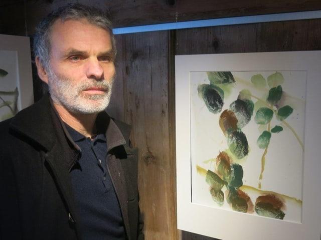 Der Maler Ivo Vonlanthen steht vor einem Bild, das wie ein Zweig mit Blättern aussieht.