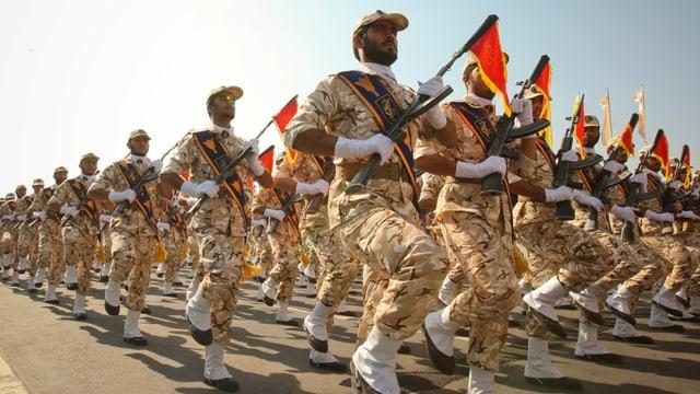 Soldaten in sandfarbenen Kampfanzügen marschieren.