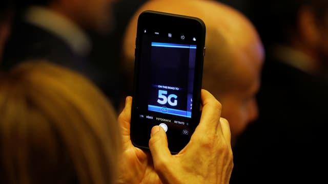 Eine Frau hält ein Smarphone in die Luft auf dem die Bezeichnung «5G» zu sehen ist.