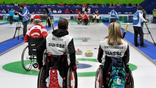 Blick über ein Curlingspielfeld. Im Vordergrund zwei Rollstuhlfarer, hinten Curlingsteine.