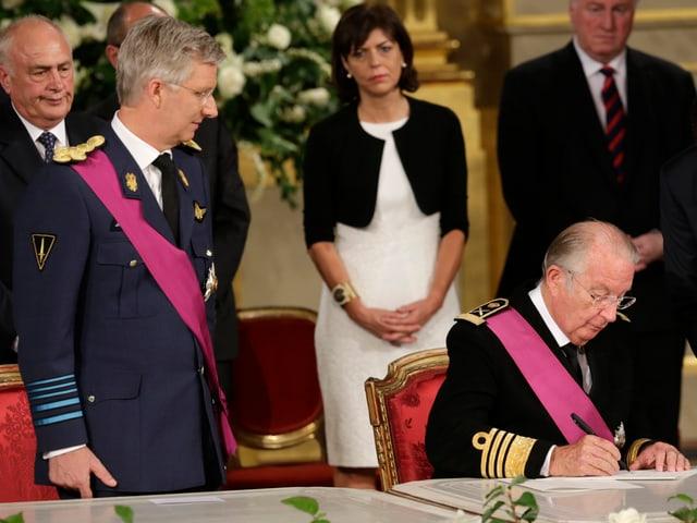 Albert unterschreibt ein Dokument, sein Sohn Philippe steht daneben.