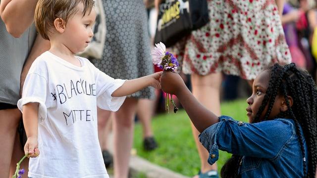 Ein weisses und ein schwarzes Kind geben sich Blumen.