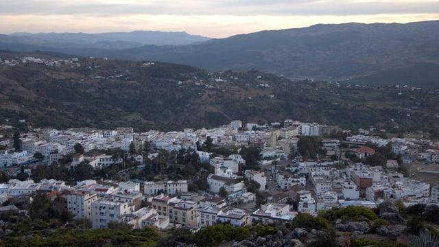 Blick auf dei Stadt Chefchaouen im Rif-Gebirge im Norden Marokkos in der Abenddämmerung.