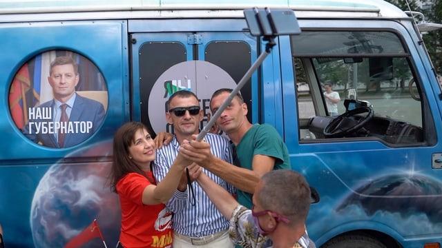 Drei Personen fotografieren sich vor einem blauem Kleinbus.