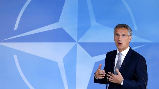 Nato-Generalsekretär Jens Stoltenberg spricht vor einer blauen Nato-Flagge.