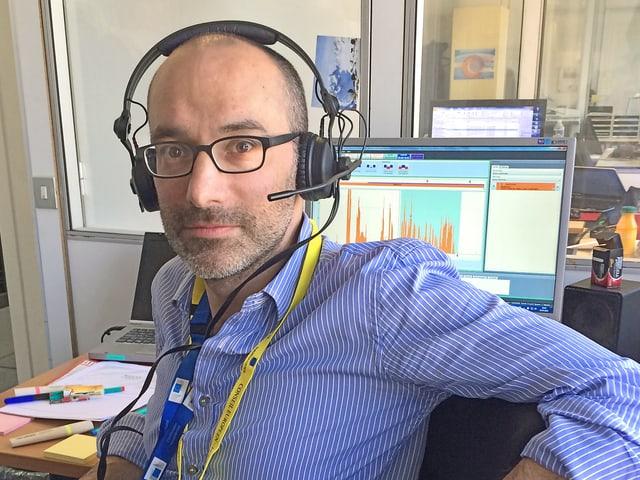 Mann mit Kopfhörern vor Computerbildschirm.