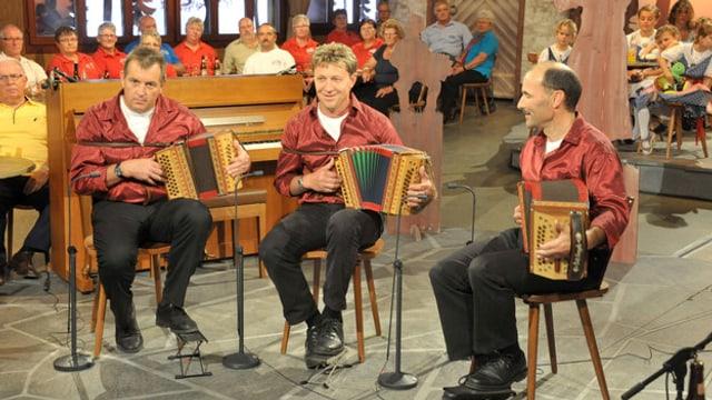 Drei Musikanten der Aentlibuecher Giele mit ihren Schwyzerörgeli während eines Auftritts in einer Fernsehsendung.