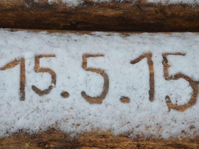 Auf Holz steht das Datum von Hand in den Schnee geschrieben.