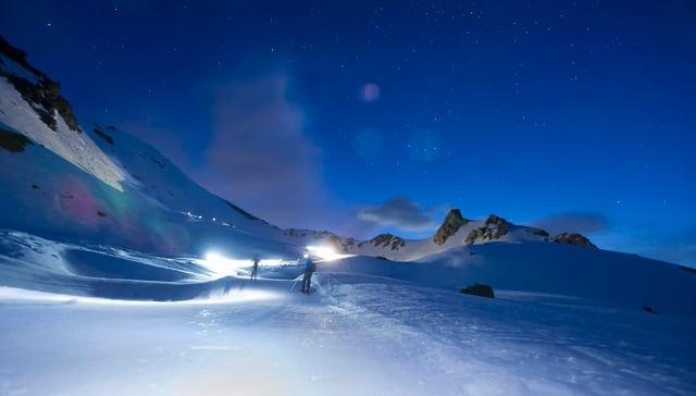 Nacht, Hochgebirge, viel Schnee, sternenklarer Himmel. Alles in schönen Blautönen. In der weite der Landschaft marschieren zwei Skitourenläufer.
