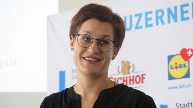 Eine junge Frau mit kurzem Haar und Brille