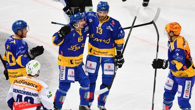 4 giugaders da hockey en vestgadira blaua sa legran d'in gol