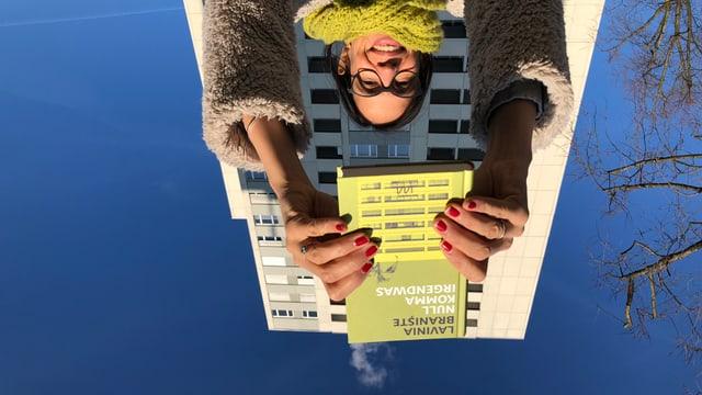 Annette König hält den Roman «Null Komma Irgendwas» von Lavinia Braniște in die Luft. Im Hintergrund ein Hochhaus, das dem auf dem Buchcover gleicht.