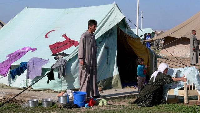 Eine Familie vor einem Zelt in einem Flüchtlingscamp.