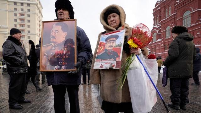 Zwei alte Russen tragen Bilder von Stalin durch die Strassen von Moskau