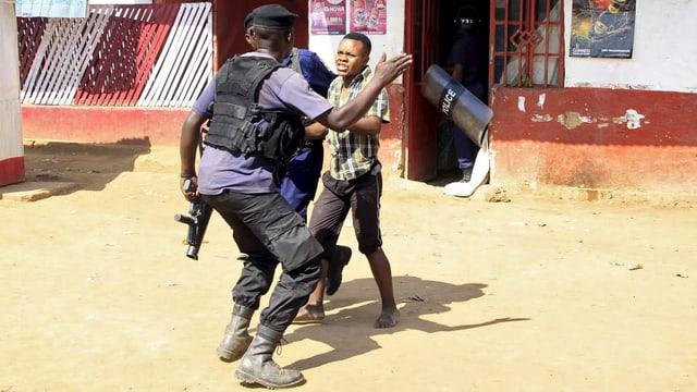 Ein Polizist mit erhobener Hand von hinten und ein Jugendlicher, der von einem anderen Polizisten festgehalten wird.