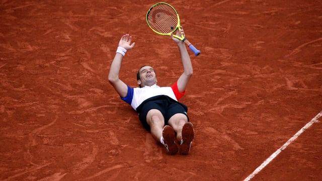 Richard Gasquet liegt nach seinem Sieg gegen Kei Nishikori auf dem roten Sandplatz auf dem Rücken.