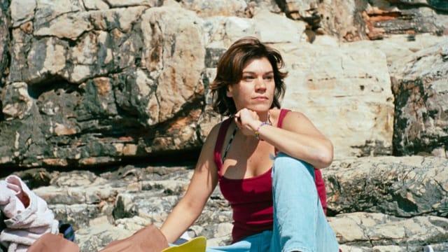 Filmszene: Eine Frau mit halblangen Haaren sitzt vor einem Felsen und schaut in die Ferne.