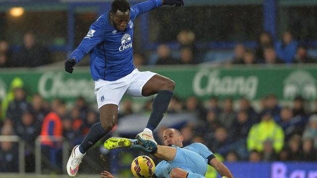 Romelu Lukaku ist vor Pablo Zabaleta am Ball, der auf den Rasen fällt.