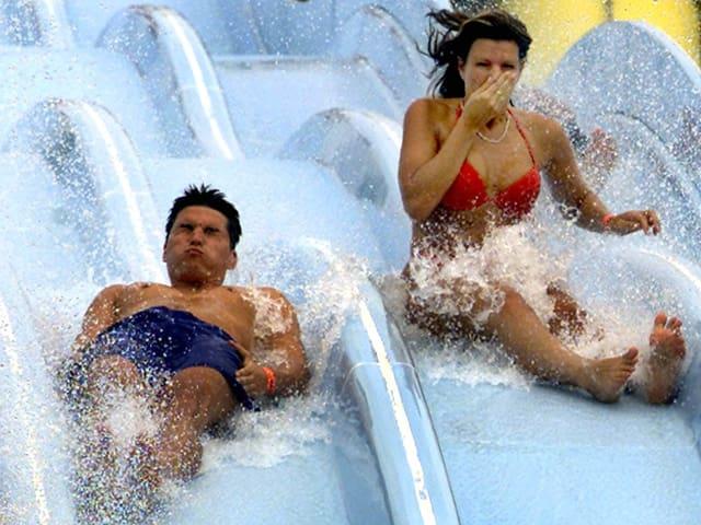 Ein Mann und eine Frau rutschen auf einer Wasserrutschbahn und das Wasser spritzt um ihre Ohren.