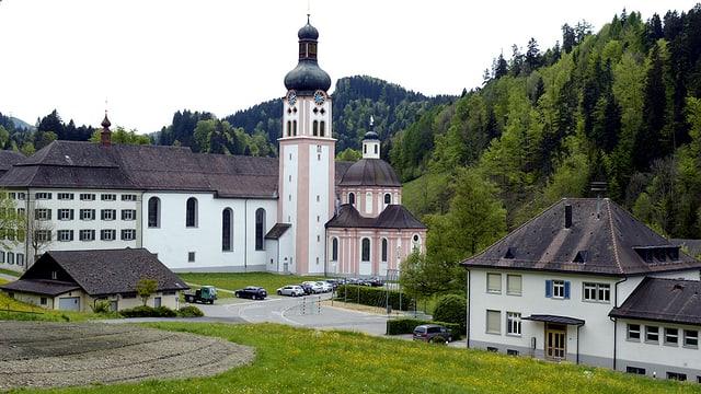 Eine Klosteranlage mit Kirche, eingebettet zwischen Wiesen und Hügel.